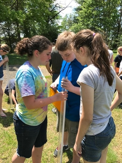Children measuring water clarity with a secchi depth tube.